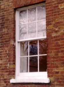 A sliding sash window recessed behind 4 inches of brickwork