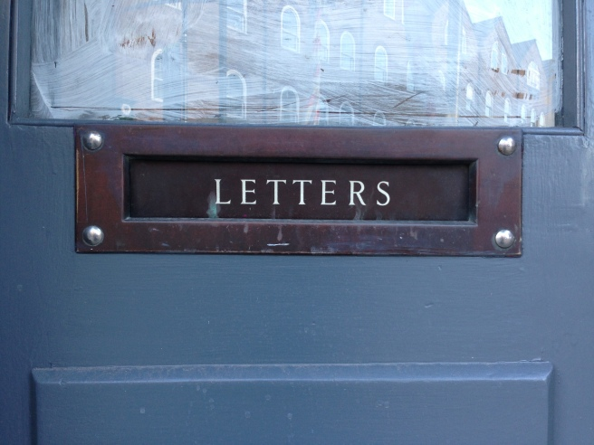 An antique, brass letterplate with white, enamel lettering